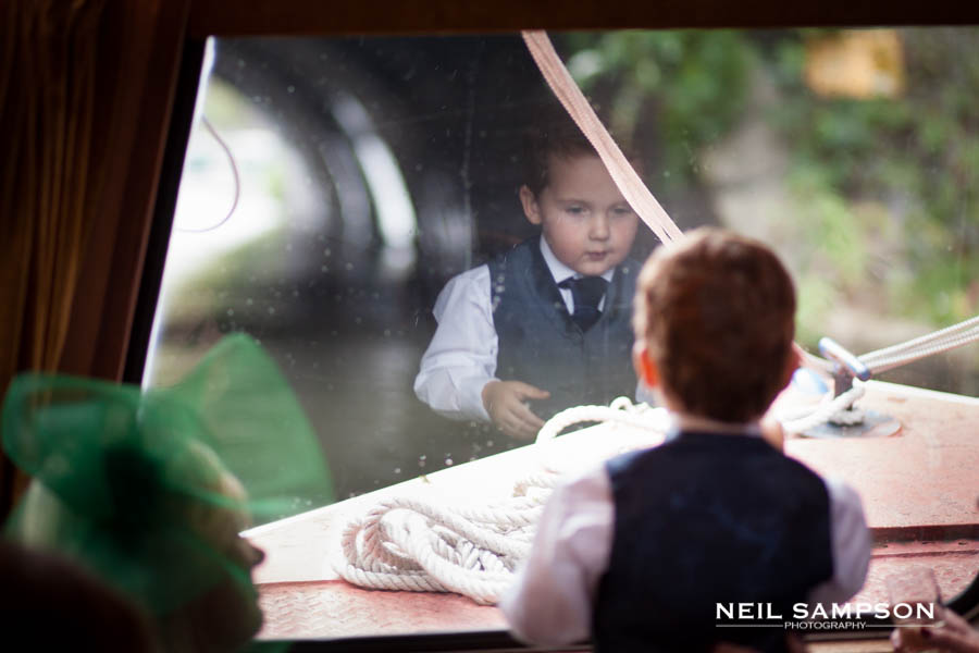 Reflection of boy in narrow boat window