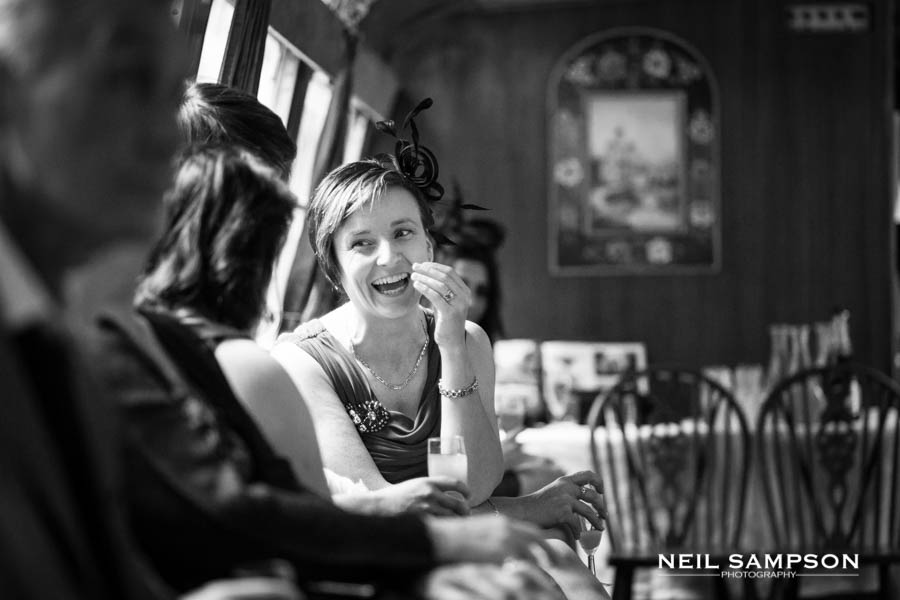 A lady laughs while talking to another wedding guest at the drinks reception