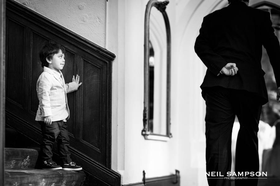 A young boy hides round the corner from an adult at Grim's Dyke Hotel