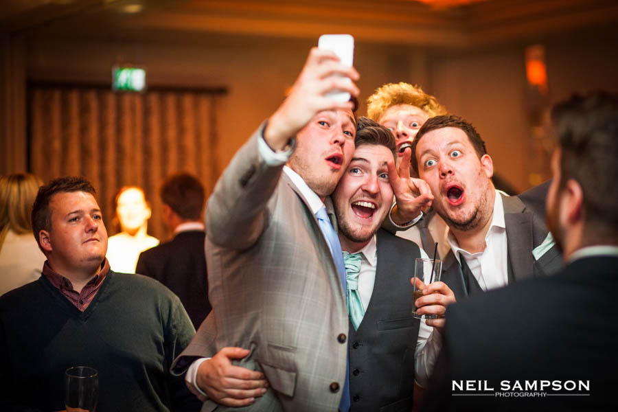 The guys take a selfie during the evening reception and their friends look on