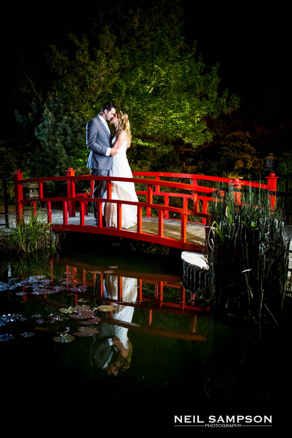 The bride and groom are lit by off camera flash as they kiss on the bridge at Sopwell House in Hertfordshire