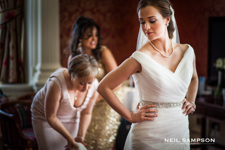The bride's mother makes final adjustments to the bride's dress just before the ceremony at Grim's Dyke Hotel
