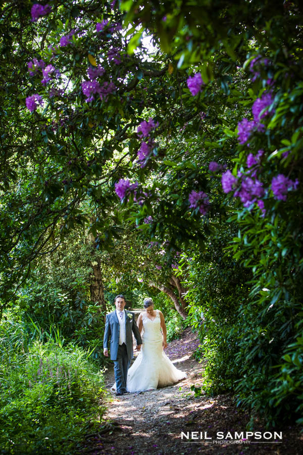 A bride and groom hold hands and walk along a floral woodland path at Grim's Dyke Hotel in Harrow