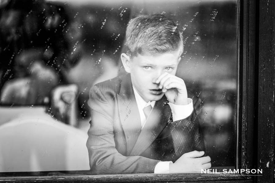 A boy looks out at the photographer through a rain covered window