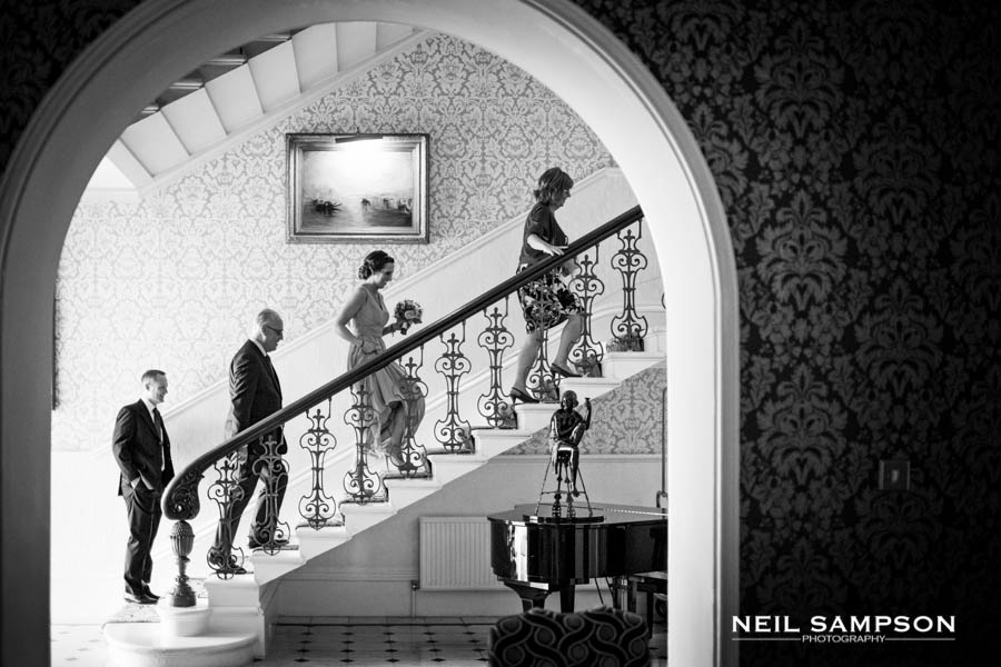 4 people walk upstairs and are framed by an arch at the Petersham Hotel in Richmond