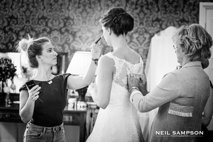Final preparations for the bride as her mother ties up her dress and the make up is touched up