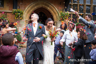 The bride and groom are showered in colourful confetti at Grim's Dyke Hotel in Harrow