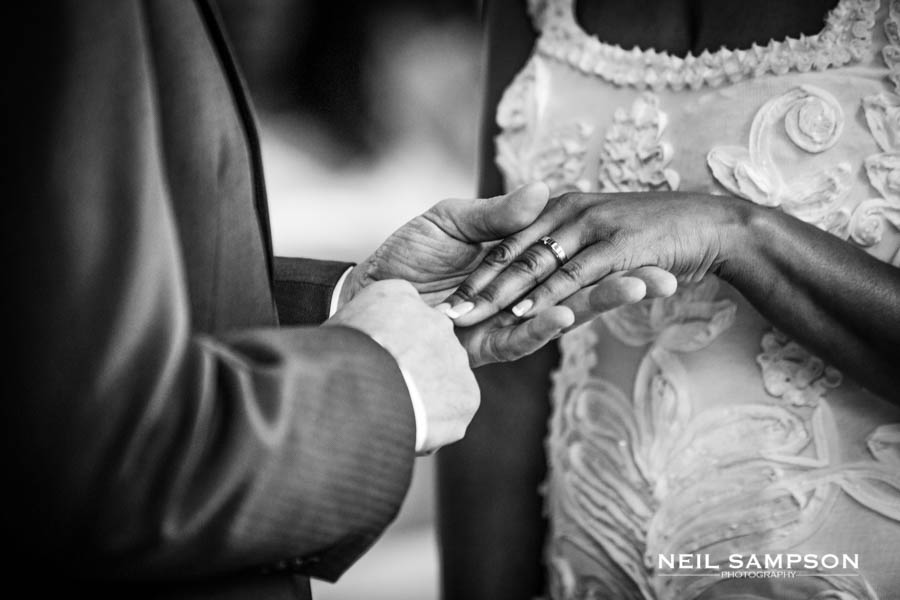 A close up photo of the groom holding the bride's hand after putting the ring on her finger