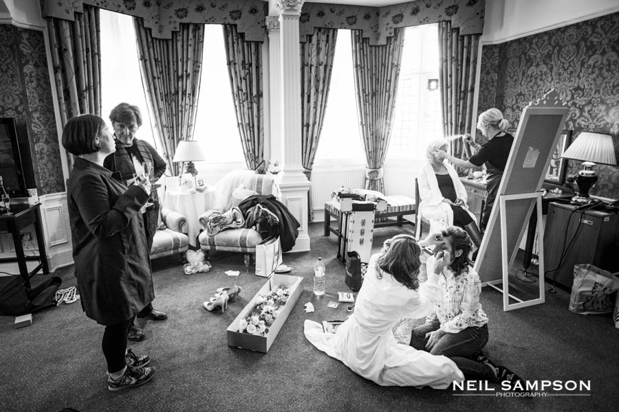 A busy room as the bride and bridesmaids get ready before the wedding
