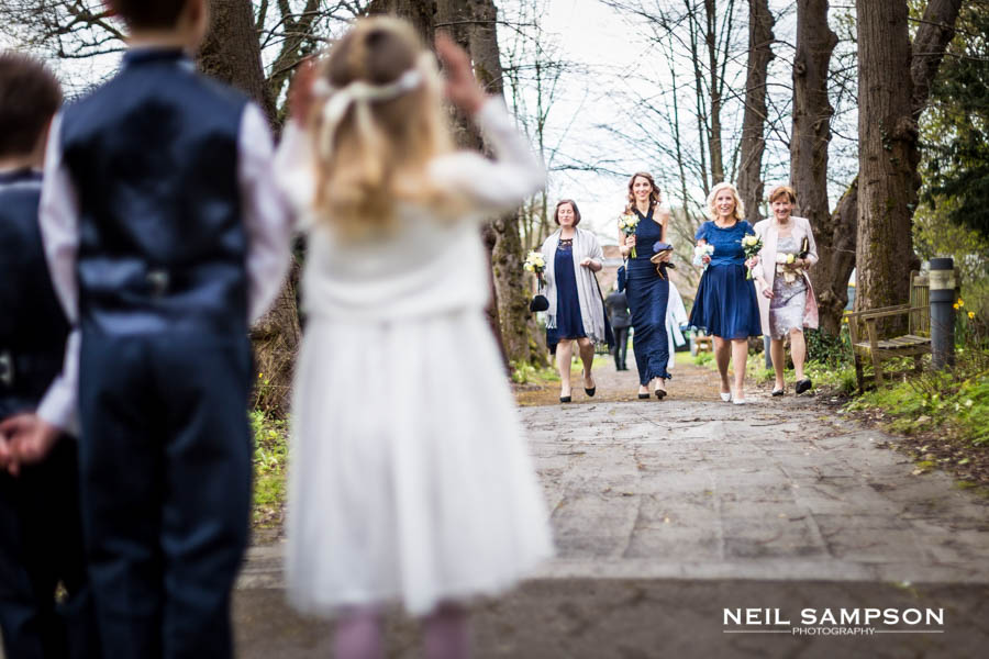 The bridesmaids walk down the path at the church while the flower girl and page boy looks on