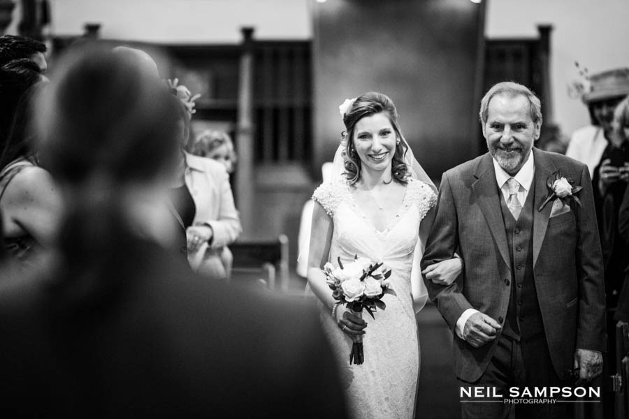The bride smiles at the groom as she walks down the aisle in church