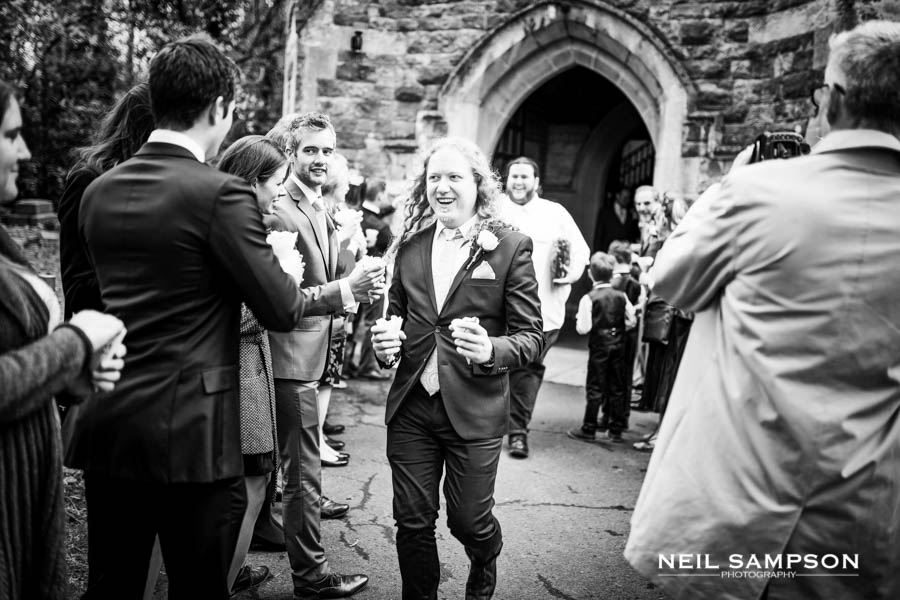 A groomsman smiles as he comes out of the church holding confetti