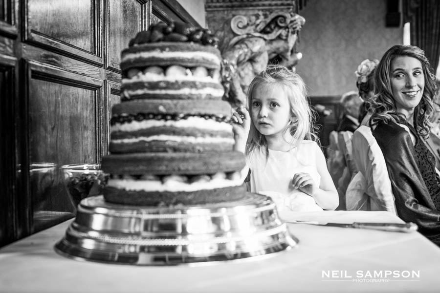 The flower girl checks out the cake as a bridesmaid looks on
