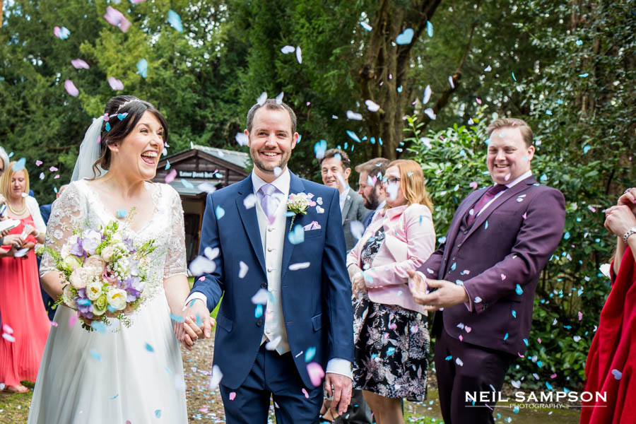 The bride and groom laugh during confetti at Latimer Church