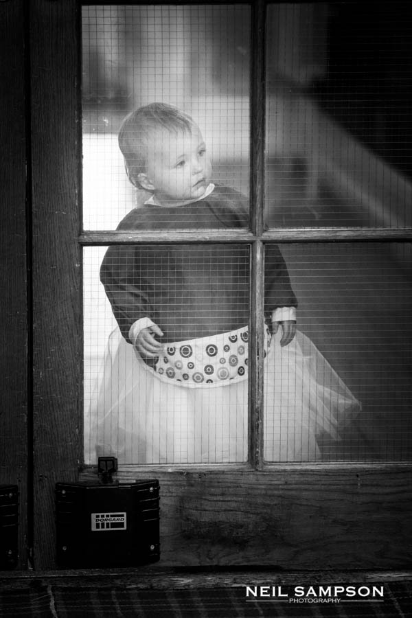 A small child looks through glass doors