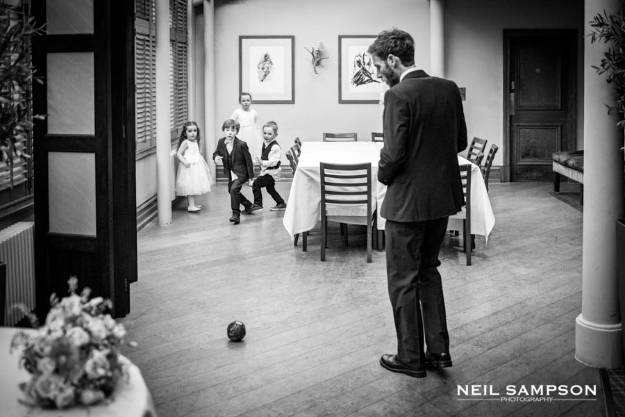 An adult guest looks on while kids play football at the wedding reception