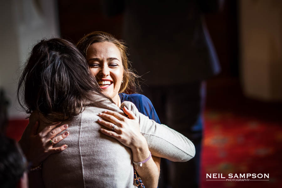 Two female friends hug each other at a wedding in Hertfordshire