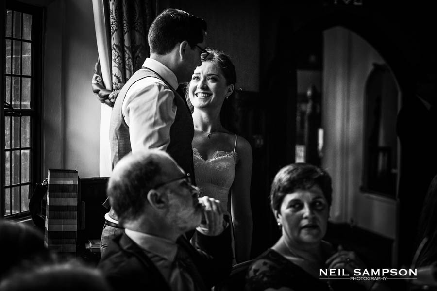 A bride and groom smile at each other in black and white