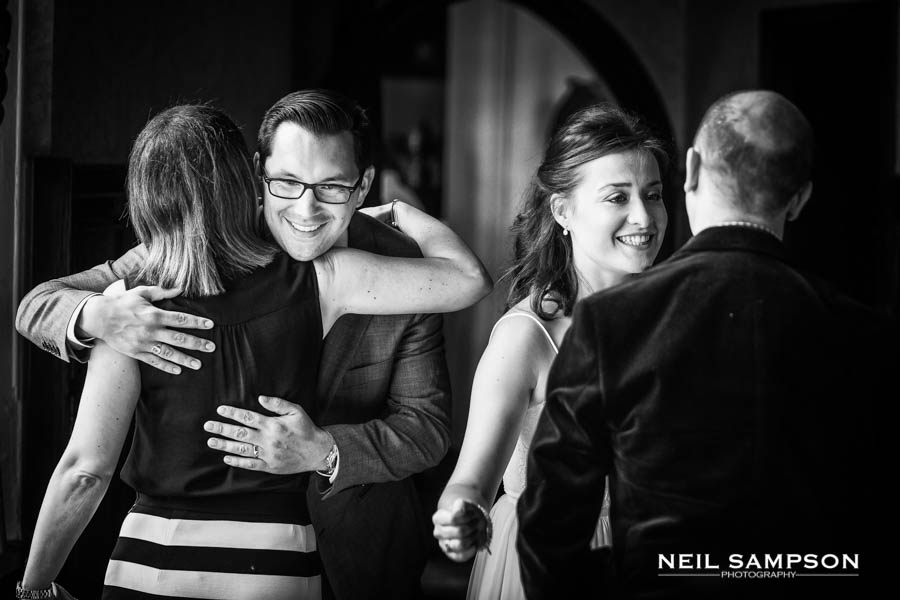 A black and white photo of guests greeting the bride and groom
