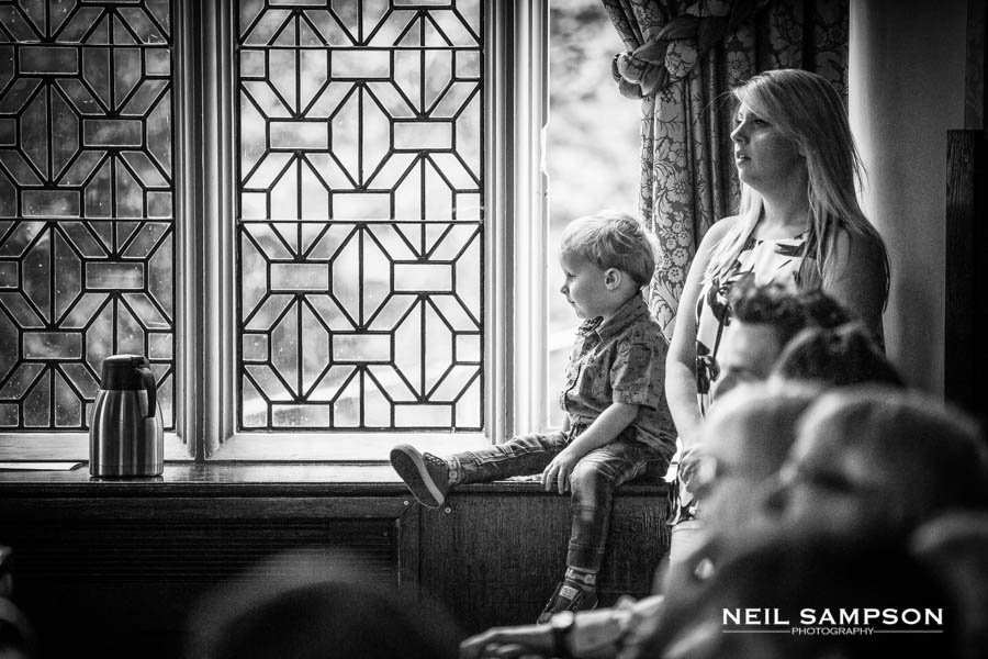 A boy sat on a windowsill during the wedding speeches