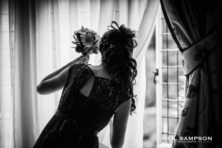 The bridesmaid is silhouetted against the window as she looks out
