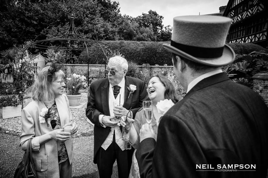 This group laughs during the wedding drinks reception at Grim's Dyke hotel