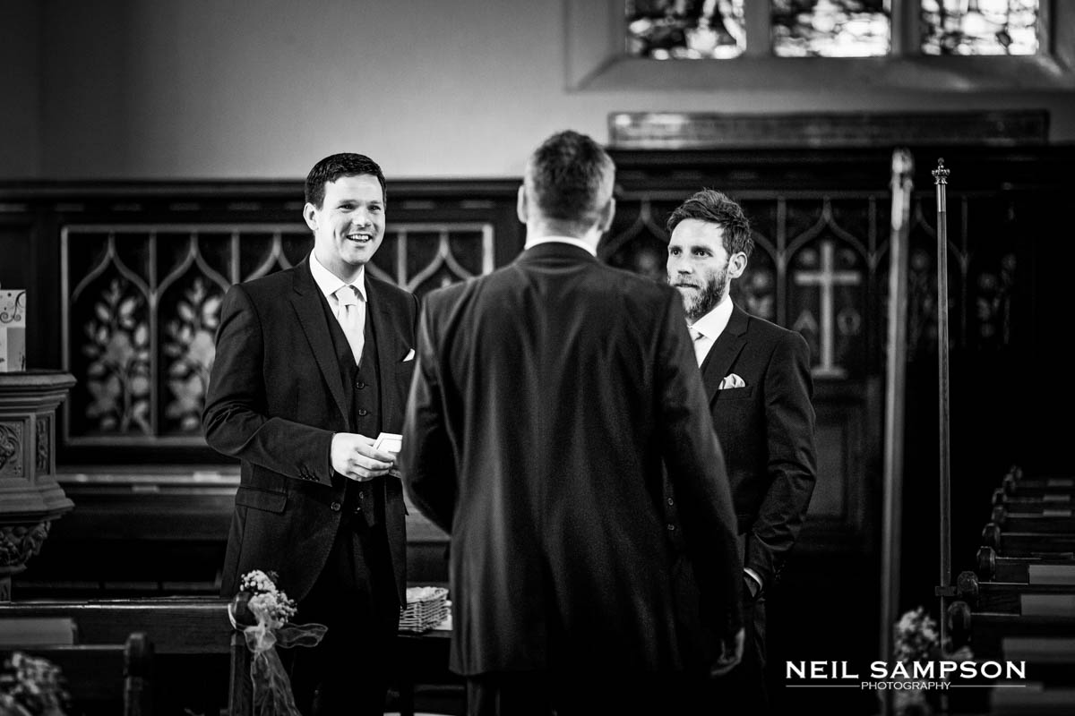 The ushers talk in the church before the ceremony in Latimer, Buckinghamshire