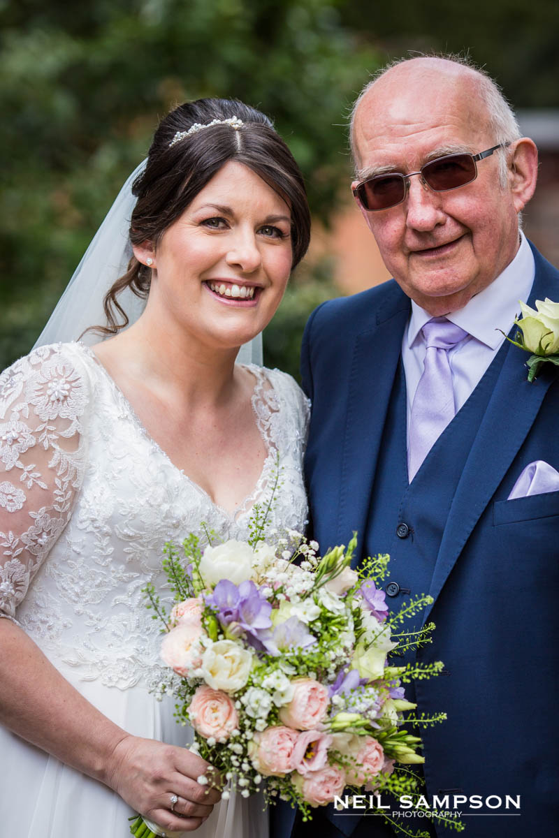 The bride poses with her father outside the church in Buckinghamshire
