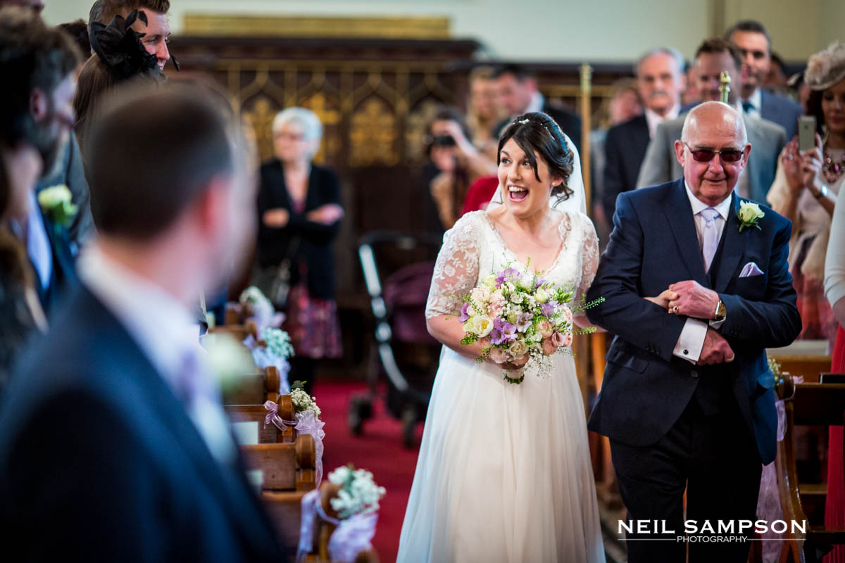 The bride arrives at Latimer Church with her father while the groom looks on