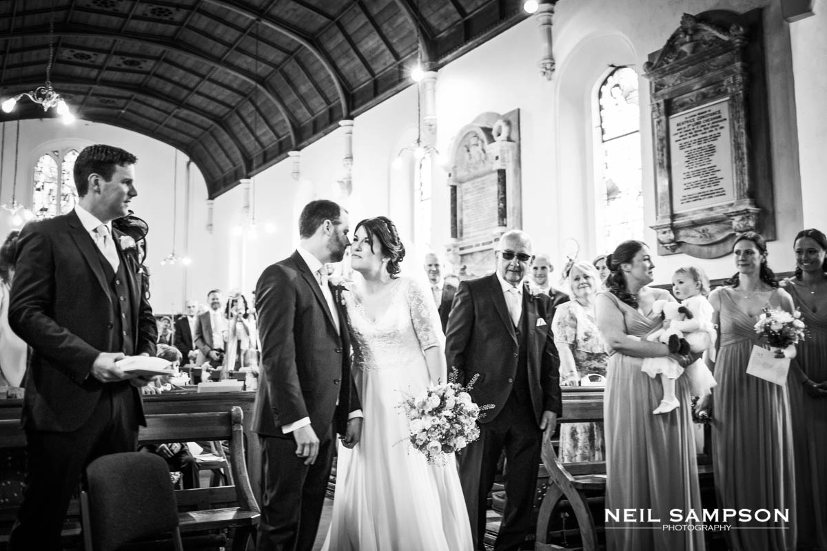 The bride and groom kiss at the start of the wedding ceremony at Latimer Church