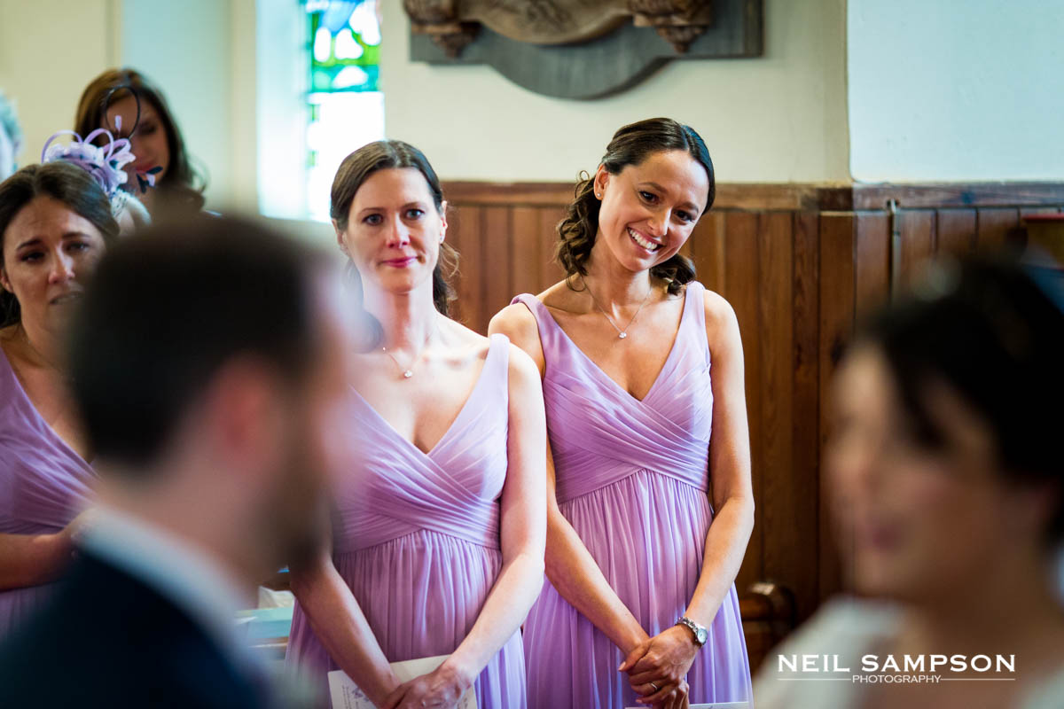Bridesmaids smile at the bride and groom at Latimer Church