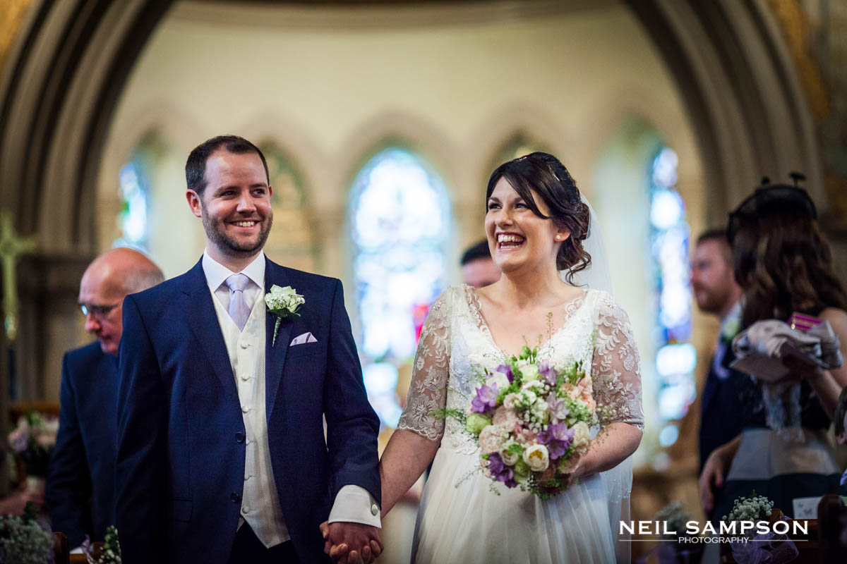 The bride and groom walk down the aisle at Latimer church
