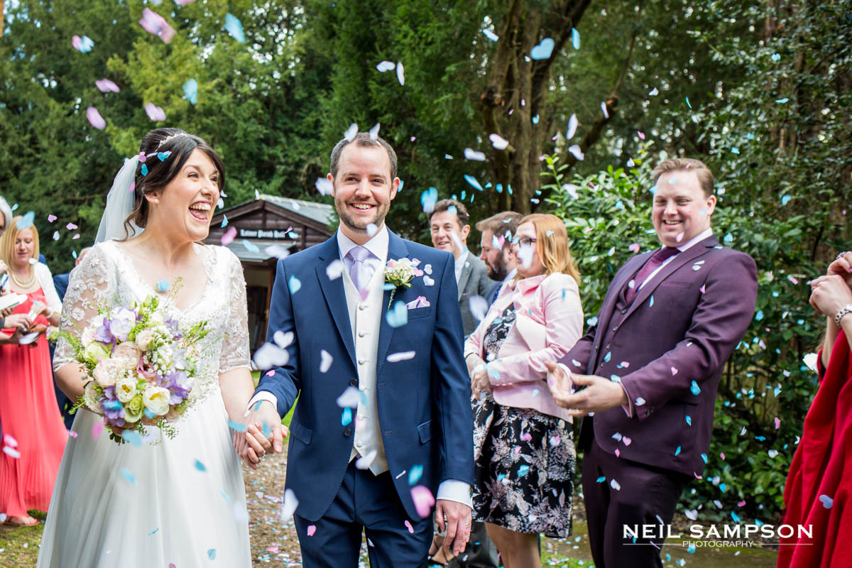 The bride and groom enjoy the confetti at Latimer Church