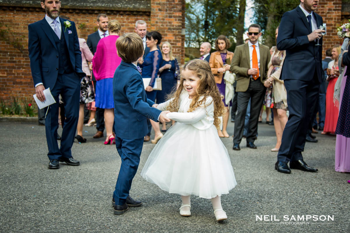 The page boy and flower girl dance during the drinks reception at Latimer Place