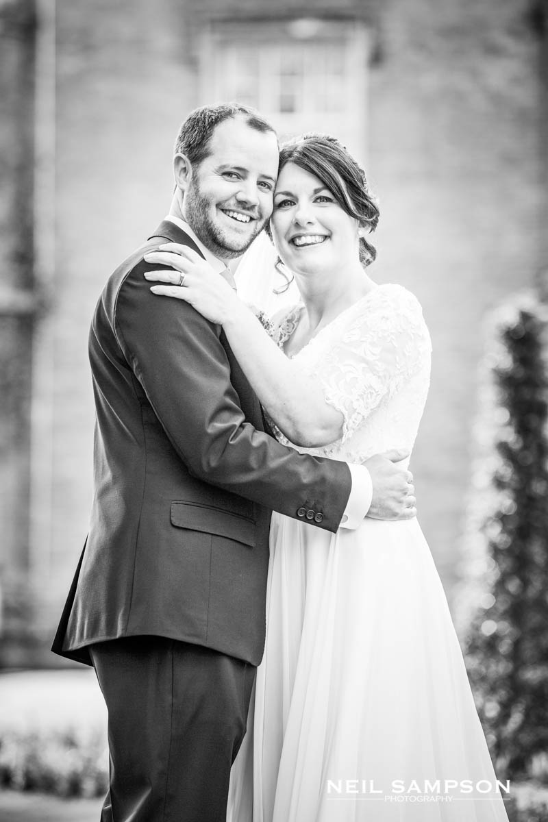 The bride and groom smile at the camera at their wedding in Buckinghamshire