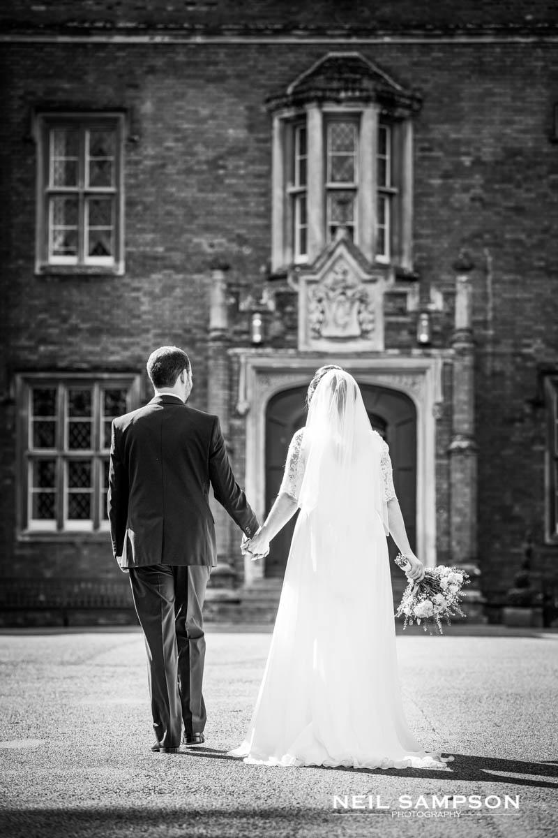 The bride and groom walk and hold hands with Latimer Place in the background