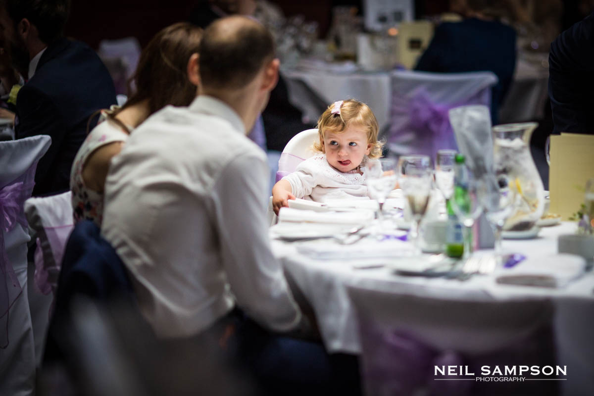 A small girl licks her lips at a wedding reception at Latimer Place