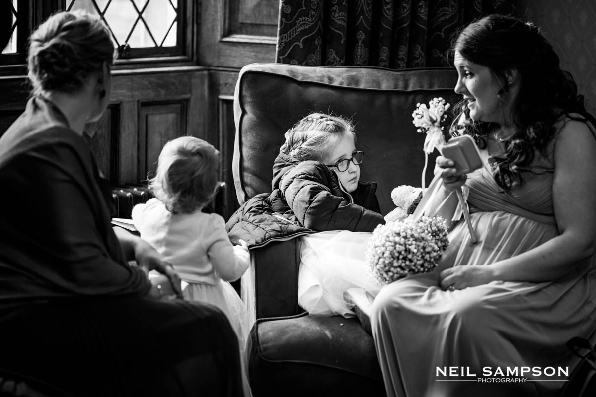 The flower girl looks cold while talking to a bridesmaid at Latimer Place