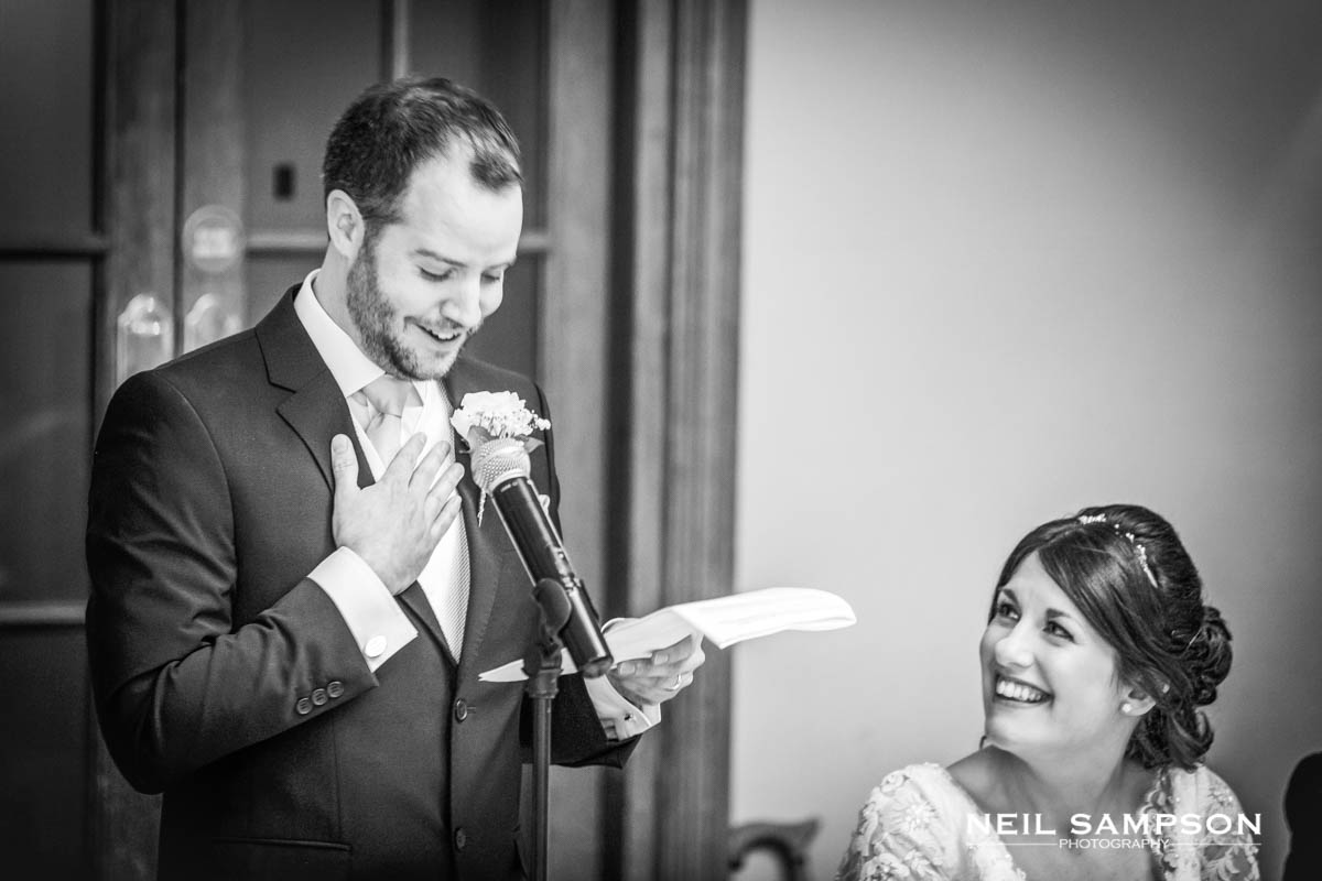 The groom wells up during his speech and his new bride smiles at him
