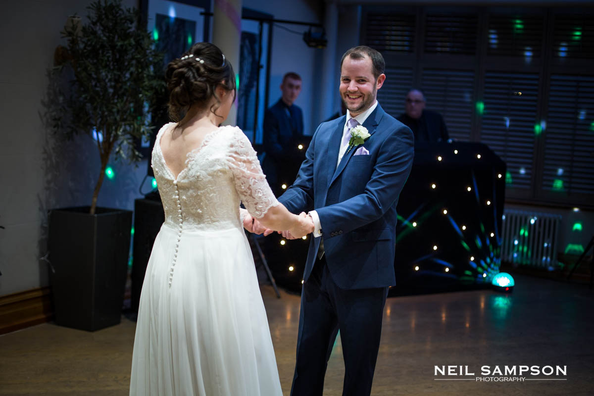 The groom smiles during the first dance at their wedding at Latimer Place