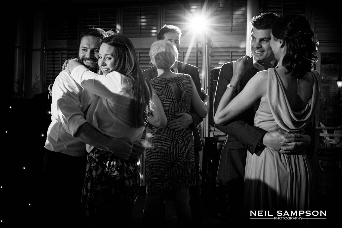 A black and white photo of guests dancing during the wedding celebrations at Latimer Place