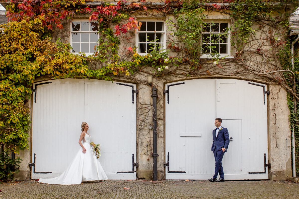 Bride and groom look lovingly at each other in front of large white wooden doors at Northbrook Park in Farnham