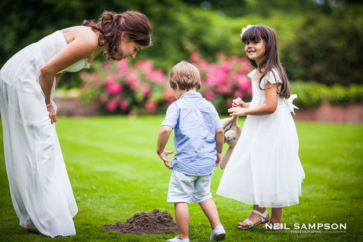 the bride and young children interact in the gardens at grim's dyke hotel
