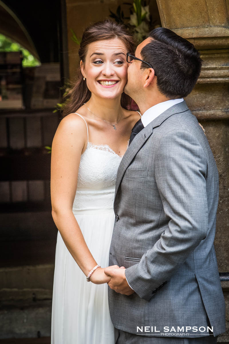 the groom kisses the bride on the cheek and she smiles genuinely