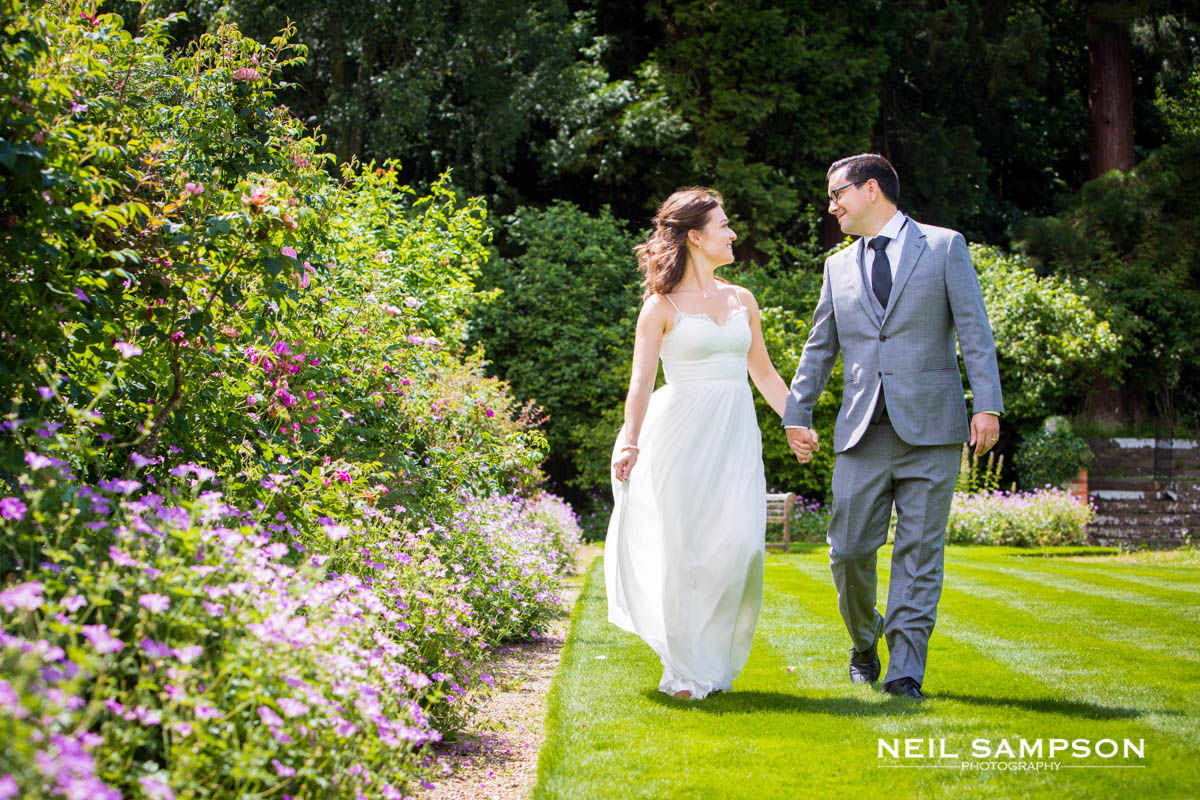 the bride and groom walking and holding hands in the rose garden at Best Western Grim's Dyke