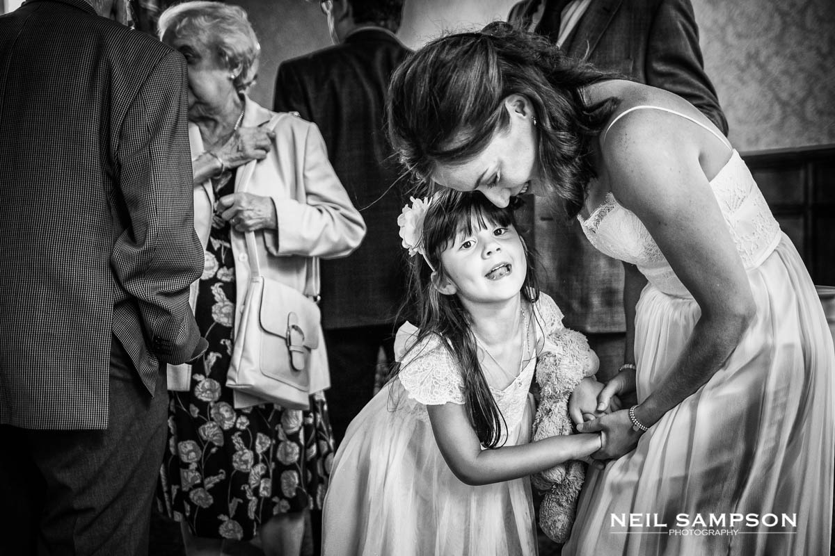 the bride and flower girl share a funny moment together