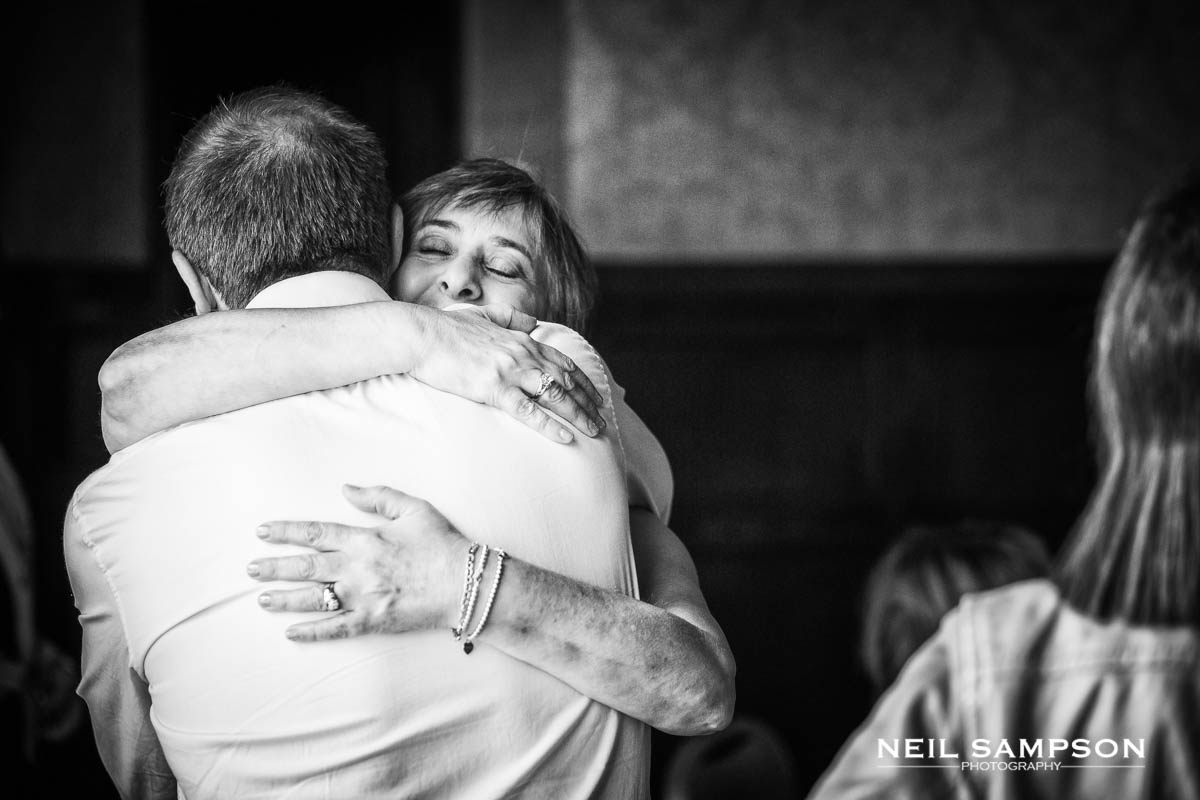 the bride's mother gives a big hug to a guest at the wedding
