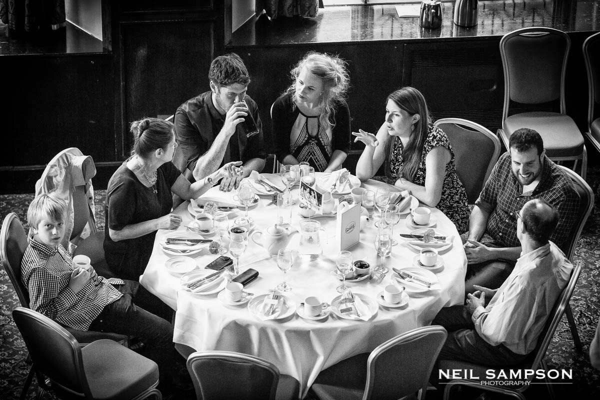 guests seated around a table during the wedding meal at grims dyke hotel