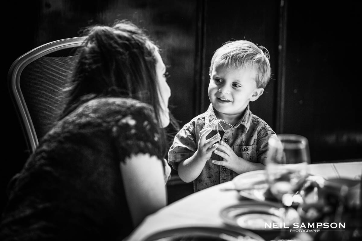 a small boy smiles at his mother during the wedding reception