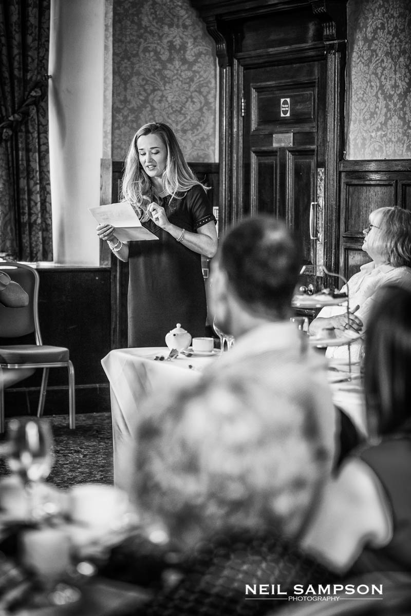 a black and white photo of the maid of honour during the wedding speeches